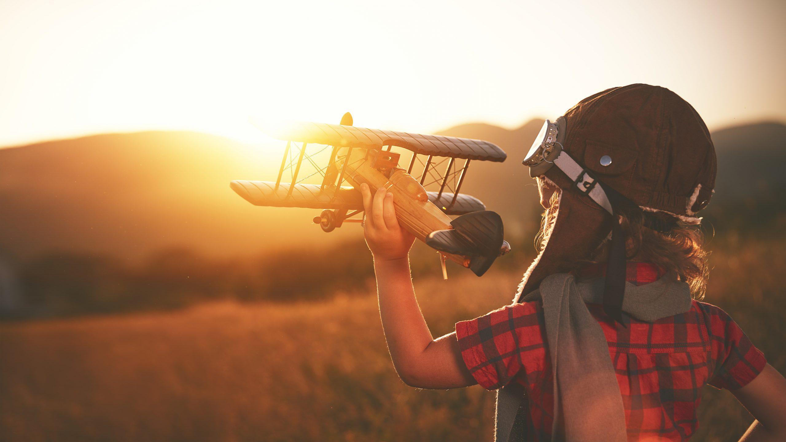 Kind mit Fliegermütze und Spielzeugflugzeug